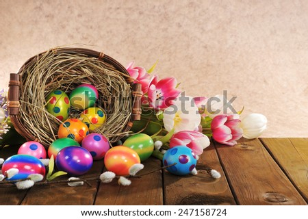 Easter nest with many colored hen�s eggs, tulip, hyacinth and pussy willow on old wooden board - stock photo