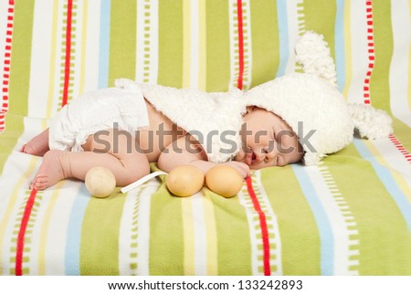 Easter newborn baby boy sleeping on blanket with fresh eggs near him