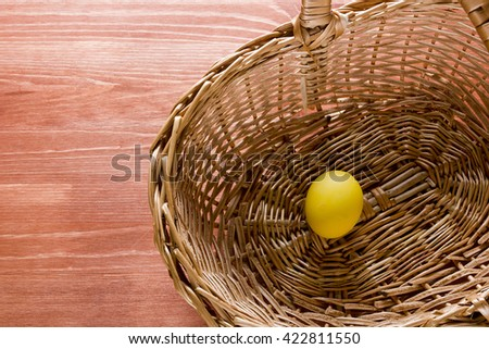 Easter painted eggs in a wicker basket on a wooden surface - stock photo