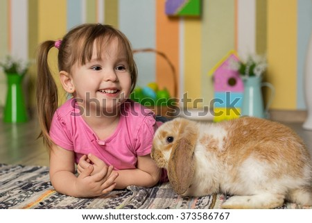Easter photo. Little cute girl play with rabbit