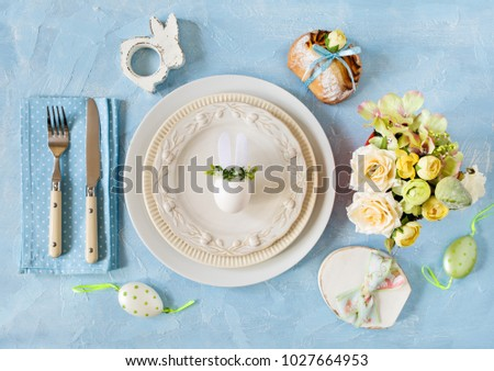 Easter place setting with easter bunny egg on a plate on blue colors.