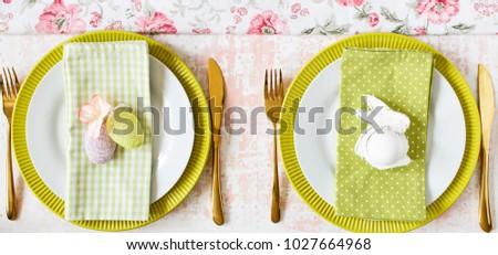 Easter place setting with easter egg on a plate on blue colors.