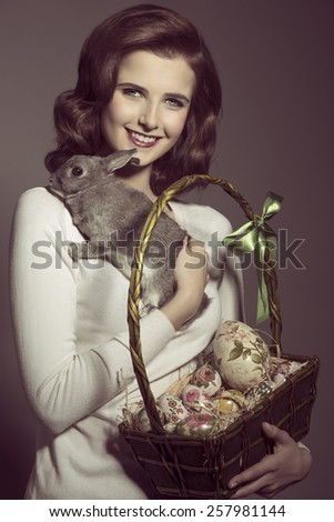 easter portrait of very pretty brunette female with vintage hair-style, posing with lovely fluffy rabbit and basket with colorful eggs  - stock photo