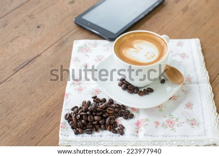 Easter rabbit drawing on latte art coffee cup - stock photo