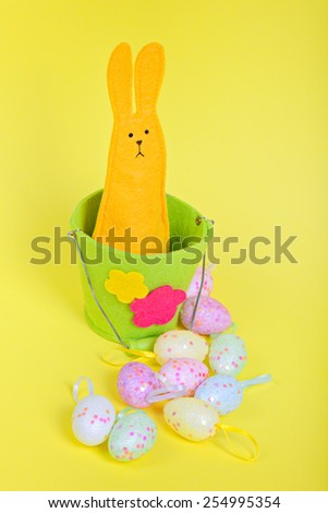 Easter rabbit in bucket and eggs on yellow paper background - stock photo