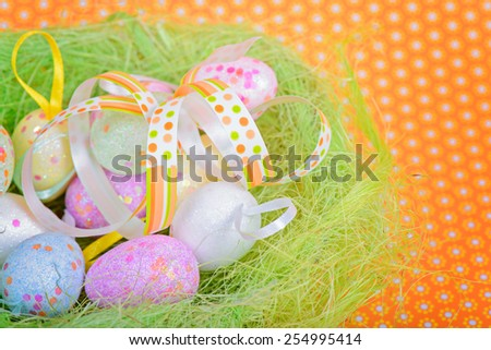 Easter ribbon and eggs in nest over orange floral background - stock photo