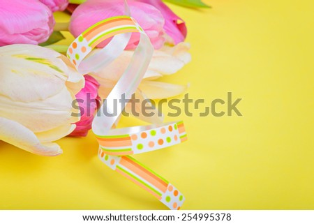 Easter ribbon with pink tulips and copy-space over yellow paper - stock photo