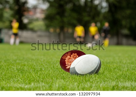 Easter rugby concept. rugby ball and a easter egg script at green turf.
