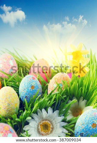 Easter scene background. Beautiful colorful eggs in spring grass meadow over blue sky with sun border design