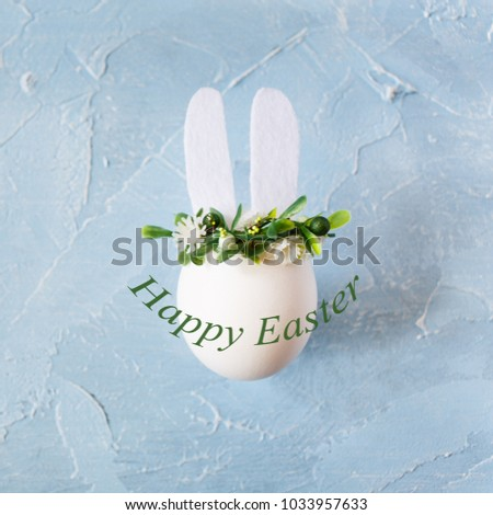 Easter shabby chic background with egg bunny in flower wreath on blue .