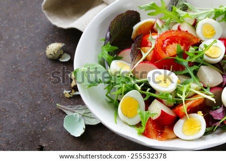 Easter Spring salad with quail eggs, tomatoes and cucumbers - stock photo