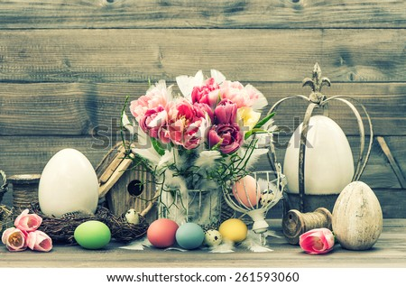 Easter still life. Decoration with tulip flowers and colored eggs. Vintage style toned picture - stock photo