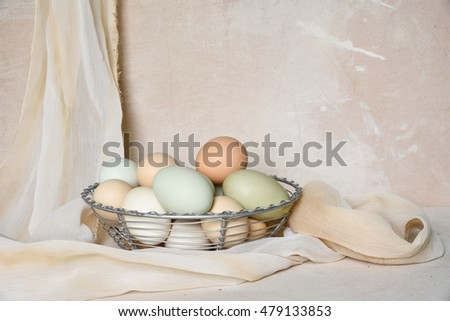 Easter still life of organic pastel colored eggs in a wire basket  on a rustic canvas background