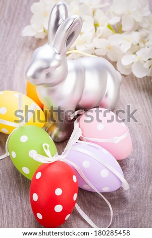 Easter still life with a metallic silver bunny ornament and eggs handpainted with colourful polka dot patterns for your seasonal greeting