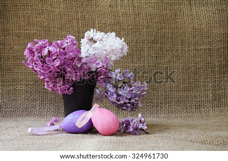 Easter still life with lush lilac flowers in ceramic vase and decorative Easter eggs. Rustic style. - stock photo
