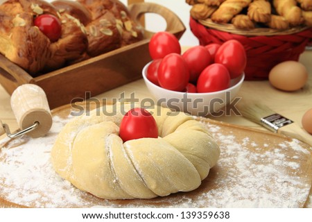 Easter sweet bread dough with red eggs - stock photo