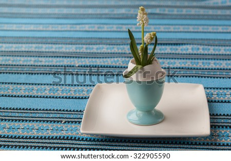 Easter table decor with white Muscari in eggshells - stock photo