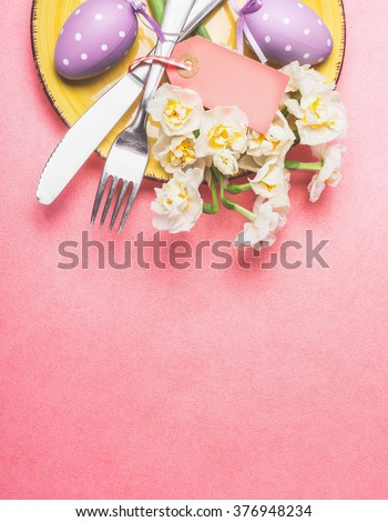 Easter table place setting with nice daffodils , cutlery, plate and eggs on pastel pink background, top view, place for text.  - stock photo