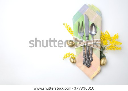 Easter table set with eggs and mimosa flowers isolated on white background.