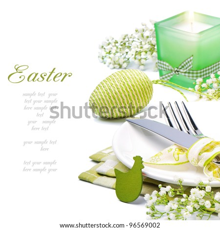 Easter table setting with candle and flowers - stock photo
