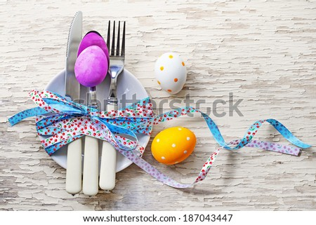 Easter table setting with colorful eggs on white wooden table/ Easter background