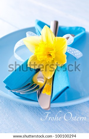 easter table setting with daffodil and cutlery and german frohe Ostern - stock photo