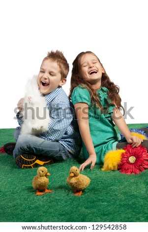 Easter theme with a young boy and girl sitting on the floor laughing together with a toy bunny and chicks.