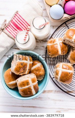 Easter traditional breakfast, hot cross bun and Easter eggs. Bright colors, view from above on wooden table. - stock photo
