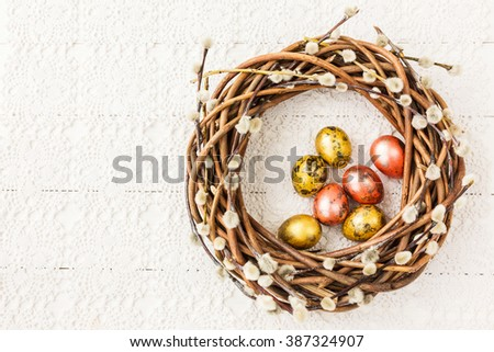 Easter willow wreath and quail  Easter eggs on white tablecloth. Top view, copy space