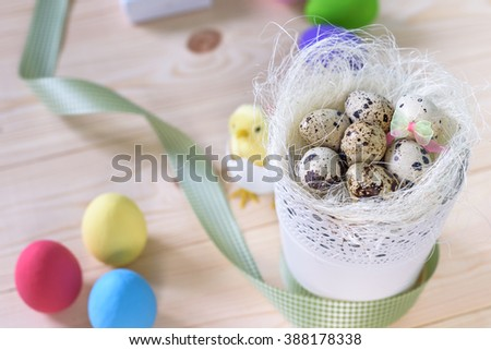 Easter with blue and white eggs in nest and gift box over white wood. Top view with copy space - stock photo