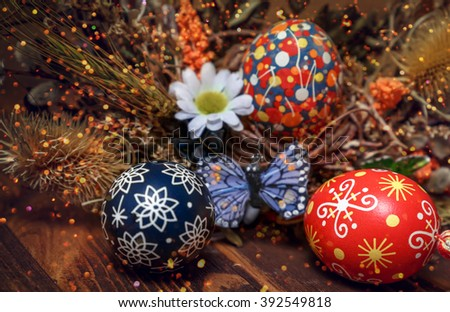 Easter wreath. Easter eggs, decorative butterflies, dry grass and blooming willow on wooden background. festive composition. Easter theme. happy Easter. close up. small depth of field - stock photo