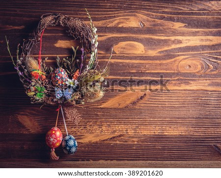 Easter wreath with easter eggs, decorative butterflies, flowers and blooming willow on the wooden background. easter decorations. Happy Easter. instagram toning effect - stock photo
