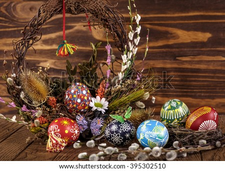 Easter wreath with easter eggs, decorative butterfly, flowers and blooming willow on the wooden background. easter decoration. happy easter - stock photo