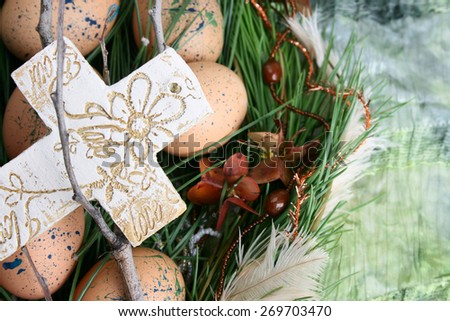 Easter wreath with eggs and decorations on green cloth - stock photo