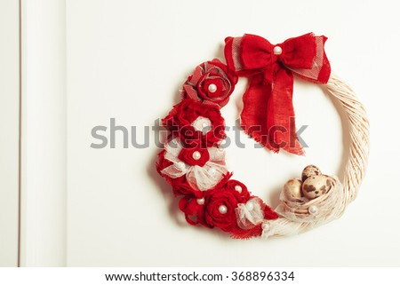 Easter wreath with red bow on the front door - stock photo