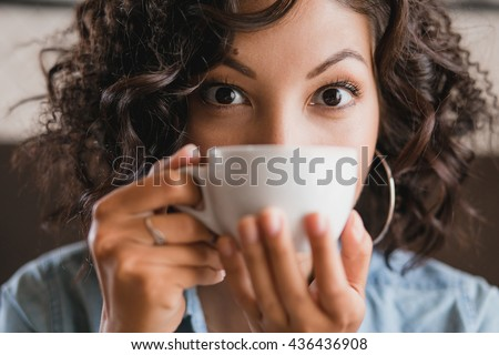 Eastern brunette curly girl drinking and smelling a cup of tea or coffee at work, hipster denim clothing - stock photo