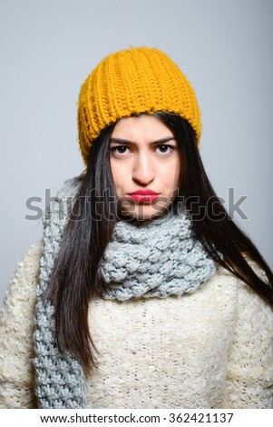 Eastern brunette girl frowned hipster in winter clothing, photo studio, portrait of a woman isolated on gray background
