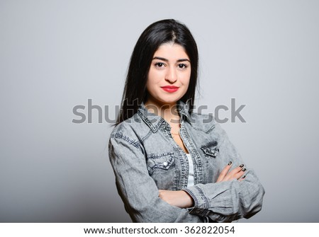Eastern brunette girl smiling with his arms crossed, hipster denim clothing, photo studio, portrait emotions - stock photo