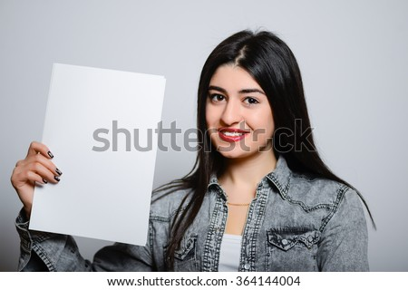 Eastern brunette girl with a blank sheet of paper, hipster denim clothes, isolated studio portrait emotions - stock photo