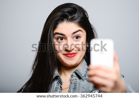 Eastern brunette photographed on a mobile phone, hipster denim clothing, photo studio, portrait emotions - stock photo