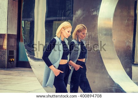 Eastern European Professional Woman working in New York, dressing in long vest, black fitted T shirt, looking down, walking passed by metal mirror wall, lost in thought. Instagram filtered effect. - stock photo