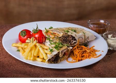 Eastern food. Arab food. Shawarma. Shawarma with potatoes and vegetables. Healthy eating, delicious food, nourishing food. - stock photo