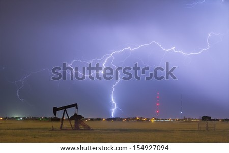 Eastern plains of the Rocky Mountain front range Weld County, Colorado, view of a pumpjack with a lightning thunderstorm strike near by.   - stock photo