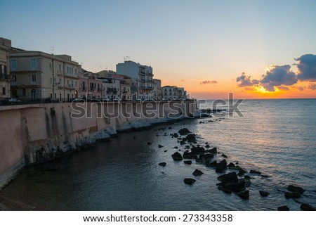 Eastern side of old Syracuse with rock and sea at dawn - stock photo