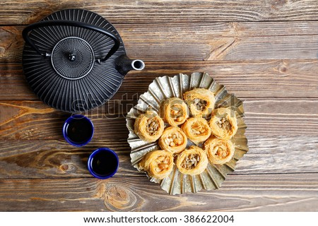 Eastern sweets baklava, teapot and two small bowls on wooden table. Top view. - stock photo
