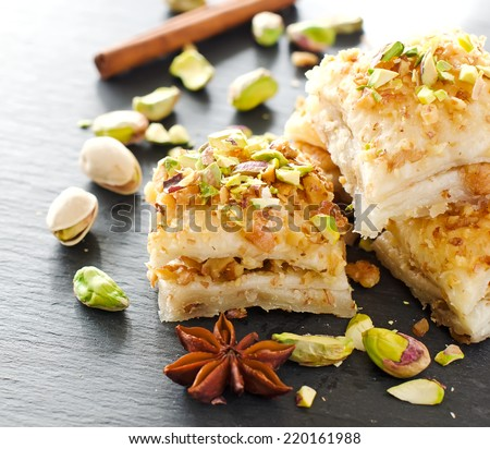 eastern traditional dessert with nuts and pistachios with a stick of cinnamon selective focus square image - stock photo