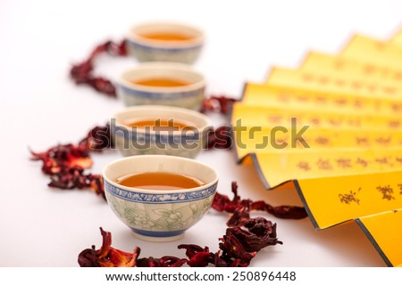 Eastern traditions. Beautiful composition of crockery teacups surrounded by flower tea and Chinese hand fan isolated on white background with selective focus  - stock photo