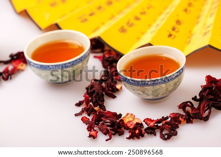Eastern traditions. Top view image of crockery teacups surrounded by flower tea composition and Chinese hand fan isolated on white background with selective focus
