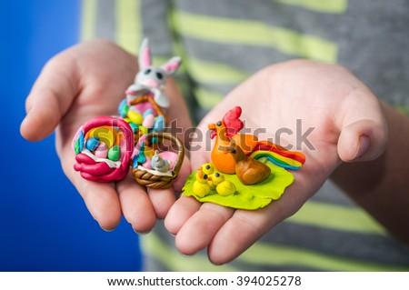 Easters plasticine figures in kid hands - stock photo