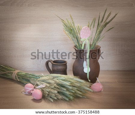 Easters still life from painted eggs, raw wheat and clayware.